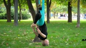 A menina em um parque contratou na ioga aérea foto de stock