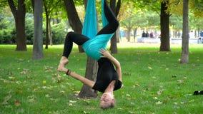 A menina em um parque contratou na ioga aérea fotos de stock royalty free