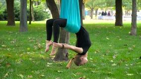 A menina em um parque contratou na ioga aérea Foto de Stock Royalty Free