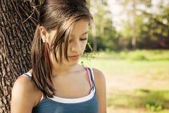 Menina em um pensamento do parque Fotografia de Stock Royalty Free