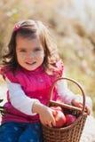 Menina em um piquenique com a cesta de maçãs vermelhas Colheita, celebração de Dia das Bruxas imagens de stock