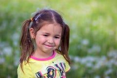 A menina em um prroda com poeira de papel dos dentes-de-leão na cabeça Imagens de Stock Royalty Free