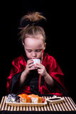 Menina em um quimono vermelho antes de uma placa com rolos Imagens de Stock