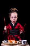 Menina em um quimono vermelho antes de uma placa com rolos Fotografia de Stock Royalty Free