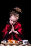 Menina em um quimono vermelho antes de uma placa com rolos Imagem de Stock Royalty Free