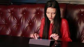 Menina em um restaurante com uma tabuleta filme