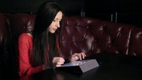 Menina em um restaurante com uma tabuleta video estoque