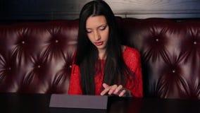 Menina em um restaurante com uma tabuleta vídeos de arquivo