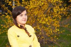 Menina em um revestimento amarelo Fotografia de Stock Royalty Free