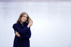 A menina em um revestimento azul anda ao longo do rio Fotografia de Stock