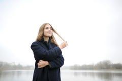 A menina em um revestimento azul anda ao longo do rio Imagens de Stock