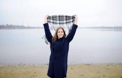 A menina em um revestimento azul anda ao longo do rio Fotos de Stock Royalty Free