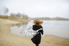 A menina em um revestimento azul anda ao longo do rio Imagens de Stock Royalty Free