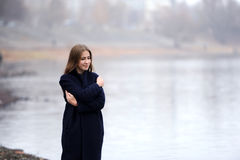 A menina em um revestimento azul anda ao longo do rio Imagem de Stock Royalty Free