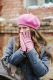 A menina em um revestimento cinzento e em uma boina cor-de-rosa, cobre sua cara com suas mãos imagens de stock