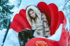 A menina em um revestimento e em uma capa curtos bege senta-se no carrossel vermelho fotos de stock
