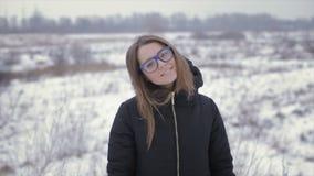 A menina em um revestimento preto em um fundo de um campo do inverno vídeos de arquivo
