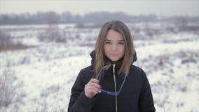 A menina em um revestimento preto em um fundo de um campo do inverno video estoque