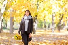 Menina em um revestimento preto em um fundo do outono com folhas imagem de stock