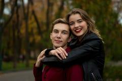 Menina em um revestimento preto, sorriso, abraçando um indivíduo pares no amor no parque do outono família em férias, data, amant imagem de stock