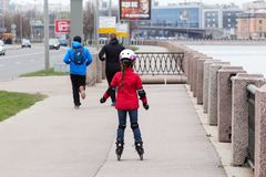 Menina em um revestimento vermelho e na calças de ganga que rollerblading fotografia de stock