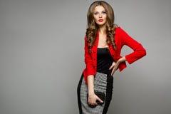 Menina em um revestimento vermelho que levanta no estúdio Imagens de Stock
