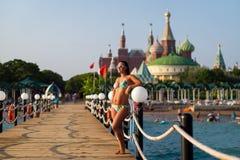 Menina em um roupa de banho no cais no fundo do hotel menina que levanta no cais de madeira na praia, contra o contexto imagem de stock