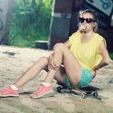 A menina em um skate fotos de stock royalty free