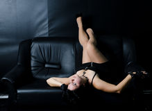 Menina em um sofá preto Fotos de Stock Royalty Free