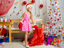 Menina em um tampão e em mitenes de Santa Claus com um saco de presentes do Natal Imagem de Stock