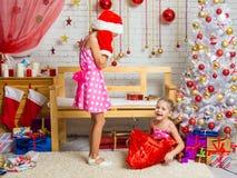 A menina em um tampão e em mitenes de Santa Claus foi surpreendida muito que fora do saco saiu de uma outra menina Foto de Stock