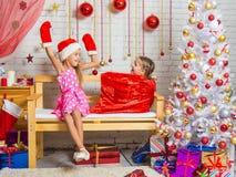 A menina em um tampão e em mitenes de Santa Claus surpreendeu que uma menina saiu do saco Fotos de Stock Royalty Free