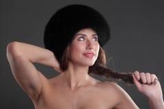 Menina em um tampão preto da pele fotografia de stock royalty free