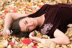 Menina em um tapete das folhas Fotografia de Stock