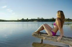 A menina em um terno de banho sobre Fotografia de Stock Royalty Free