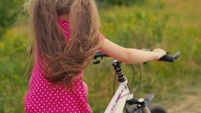 Menina em um terno vermelho que monta uma bicicleta vídeos de arquivo