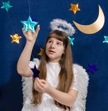 A menina em um traje do anjo joga com as estrelas Imagem de Stock