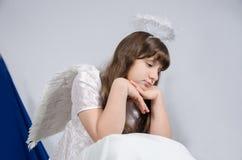 Menina em um traje do anjo que olha para baixo Imagens de Stock