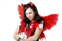 Menina em um traje do diabo com um presente imagens de stock royalty free