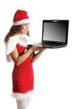 A menina em um traje Santa prende o portátil preto Imagem de Stock Royalty Free