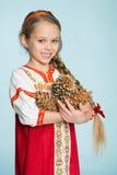 Menina em um traje tradicional do russo com cones do pinho Fotografia de Stock