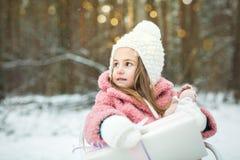 Menina em um trenó com presentes Fotografia de Stock