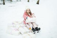 Menina em um trenó com presentes Foto de Stock Royalty Free