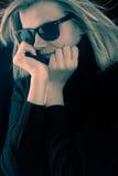 Menina em um turtleneck preto com óculos de sol retros imagem de stock