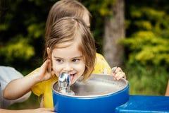 A menina em um vestido amarelo com irmãs bebe a água de uma fonte Foto de Stock