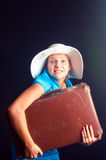 A menina em um vestido azul com uma mala de viagem Fotos de Stock
