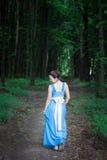 A menina em um vestido azul que anda na floresta verde gerencie ao redor Fotos de Stock Royalty Free
