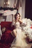 Menina em um vestido bonito com um vidro do vinho imagem de stock