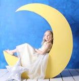 A menina em um vestido bonito senta-se em uma lua crescente Fotos de Stock Royalty Free