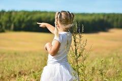A menina em um vestido branco em um campo mostra seu dedo na floresta em uma tarde ensolarada fotos de stock